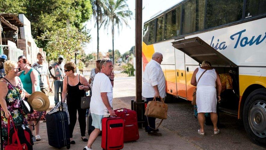 Des touristes chargent leurs bagages dans un bus pour quitter la Gambie sous état d'urgence, le 18 janvier 2017 à Banjul