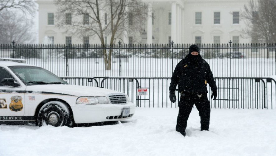 """Un officier de protection du président américain monte la garde, emmitouflé, devant la Maison Blanche, lors de la tempête de neige """"Snowzilla"""", le 23 janvier 2016, à Washington"""