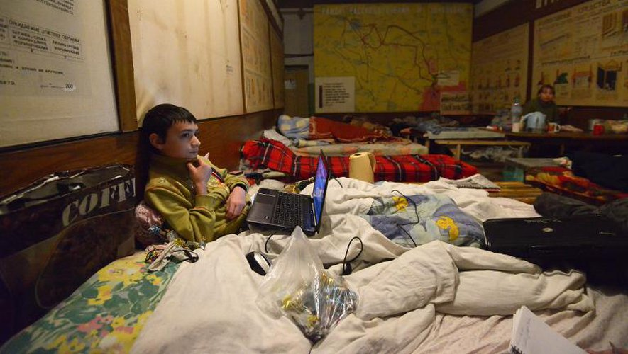 Artiom, 10 ans, allongé sur un lit, avec son ordinateur, dans un abri du quartier de Kievski, le 5 février 2015 à Donetsk, dans l'Est de l'Ukraine