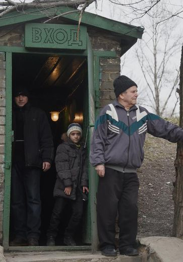 Atiom, 10 ans, à l'entrée d'un abri dans le quartier de Kievski, le 5 février 2015 à Donetsk, dans l'Est de l'Ukraine