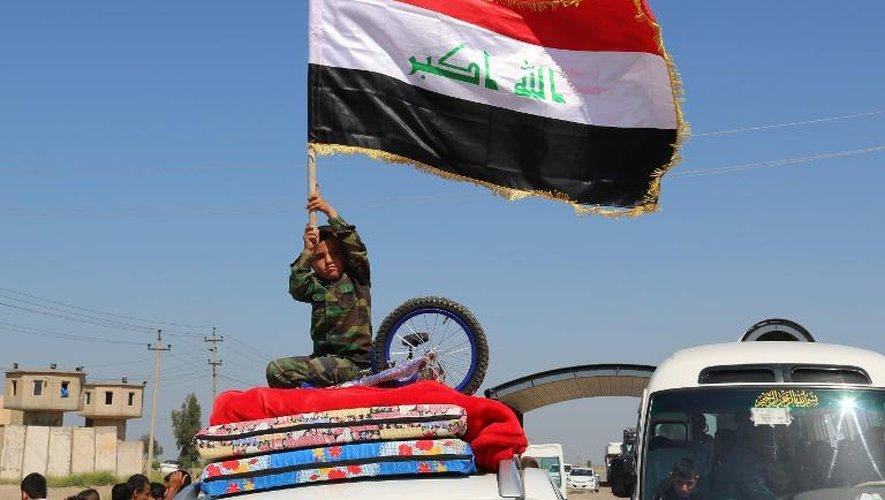 Un enfant irakien brandit le drapeau national alors que des familles déplacées quittent Kirkuk pour retourner à Tikrit, Samara et al-Alam, le 2 avril 2015