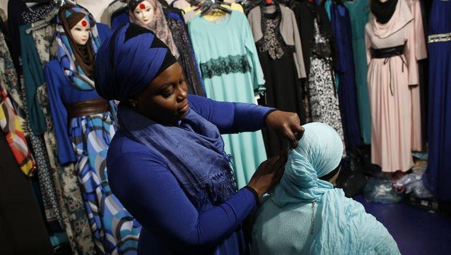 Une vendeuse aide une femme à ajuster un foulard, le 3 avril 2015 dans les allées de la rencontre annuelle des musulmans de France au Bourget