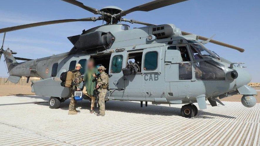 Photo fournie par les autorités françaises le 6 avril 2015 de deux soldats francais entourant l'otage neerlendais Sjaak Rijke (c), avant d'embarquer dans un hélicoptère depuis une base aérienne au Mali
