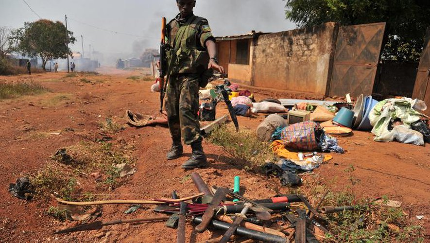 Un soldat rwandais de la Misca récupère des couteaux et des machettes après une attaque de miliciens chrétiens anti-balaka dans un quartier musulman de Bangui, le 22 janvier 2014