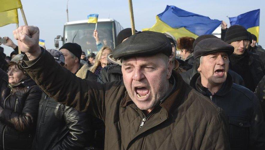 Des Ukrainiens brandissent le drapeau national au point d'accès de Tchongar, l'une des deux entrées de la Crimée par la route, le 7 mars 2014