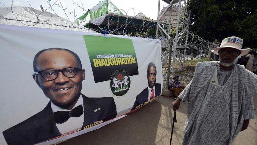 Un homme marche devant une banderole montrant les portraits du nouveau président nigérian Mohammadu Buhari et son vice-président Yemi Osinbajo le 28 mai 2015 à Abuja