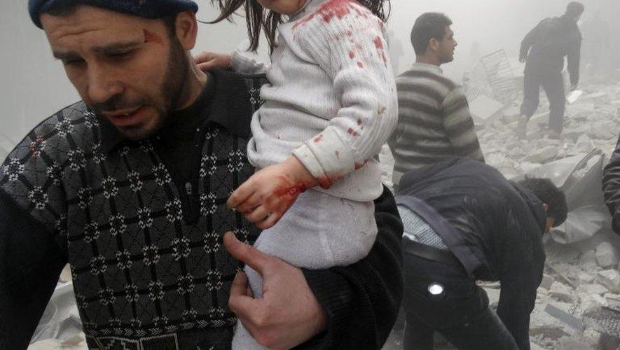 Un Syrien évacue une enfant trouvée dans des décombres après l'explosion d'un baril largué par un hélicoptère du gouvernement à Alep en Syrie, le 18 mars 2014