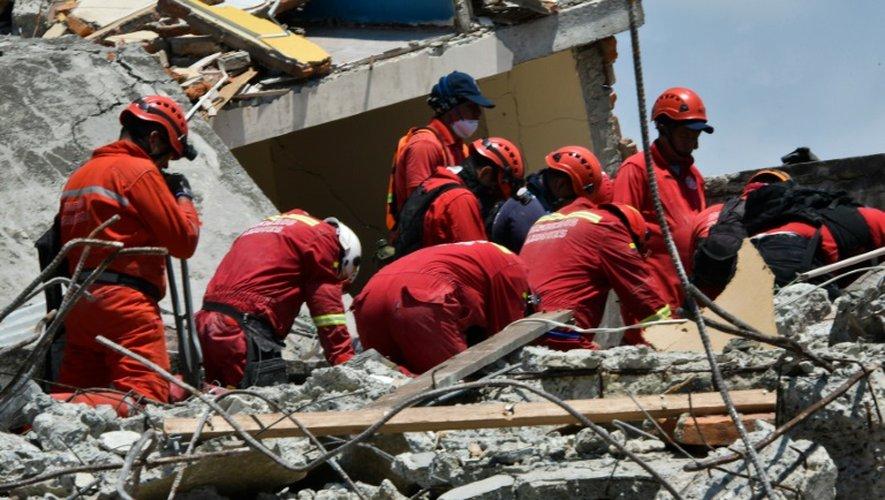 Des sauveteurs péruviens à la recherche de survivants le 18 avril 2016 dans les décombres de Manta en Equateur