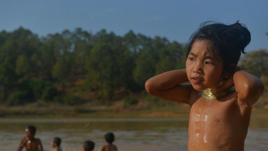 Une fillette Kayan porte des anneaux de bronze autour du cou - signe de beauté dans sa tribu - alors que d'autres enfants se baignent dans le lac, à Panpet, près de Demoso, dans l'Etat Kayah, au centre de la Birmanie, le 6 mars 2016