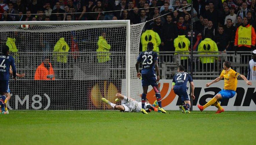 Le défenseur de la Juve Leonardo Bonucci (d) marque pour son équipe devant la défense lyonnaise impuissante en quart de finale de la Ligue Europa, le 3 avril 2014 au stade de Gerland