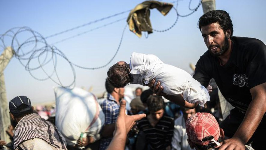 Un Syrien fait passer un enfant par-dessus les grillages séparant la Syrie de la Turquie, pour fuir les combats en Syrie, le 14 juin 2015, au poste-frontière de Akcakale
