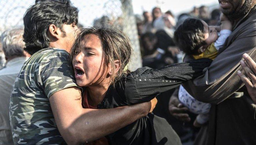 Des Syriens passent les grillages séparant la Syrie de la Turquie, pour fuir les combats en Syrie, le 14 juin 2015, au poste-frontière de Akcakale