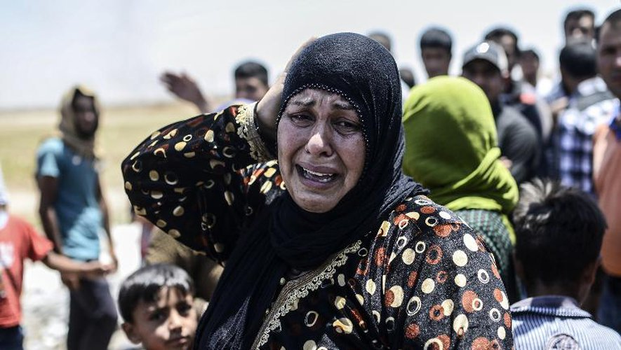 Une Syrienne en pleurs alors que la ville syrienne de Tal Abyad est bombardée, le 14 juin 2015, à la frontière avec la Turquie