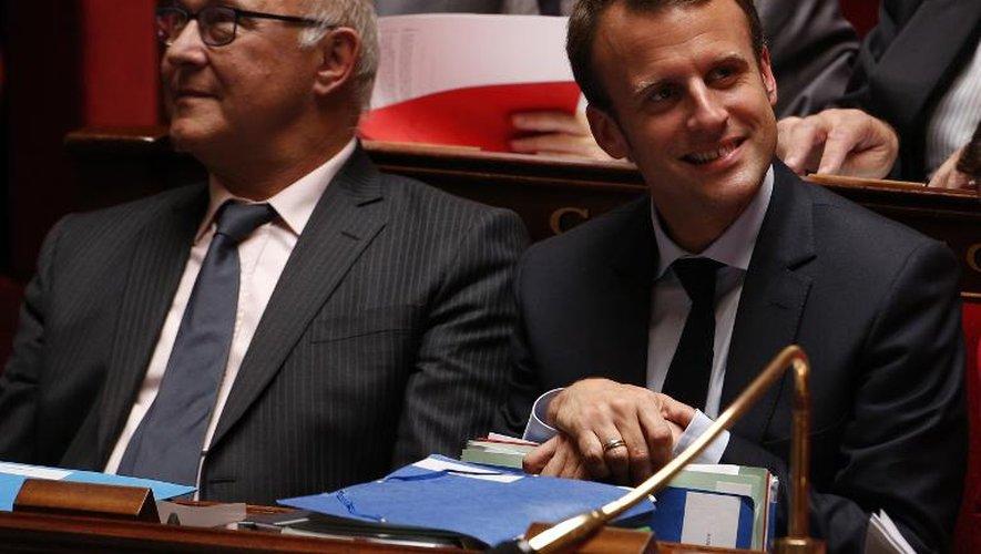 Le ministre des Finances Michel Sapin (g) et celui de l'Economie, Emmanuel Macron, à l'Assemblée Nationale, le 17 juin 2015 à Paris