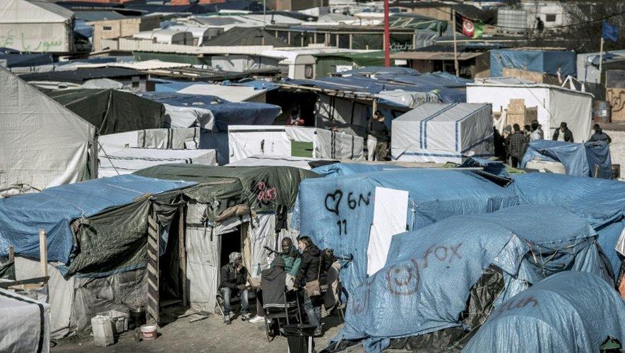 Des migrants discutent à l'extérieur de leurs tentes dans la Jungle de Calais, en France, le 30 mars 2016