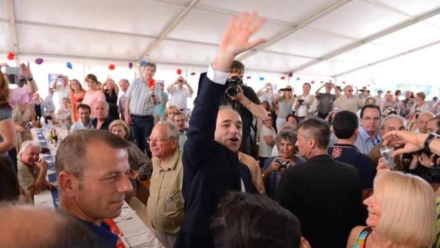 Le président de l'UMP Jean-François Copé (c) salue ses partisans, le 6 juillet 2013 à La Ferté-Imbault, pour le lancement de la fête de la Violette