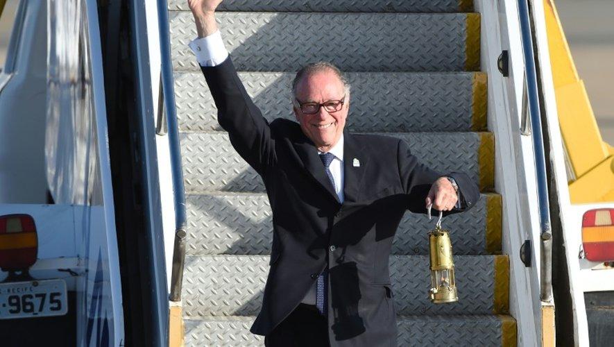 Le président du Comité olympique brésilien, Carlos Arthur Nusmann, avec la flamme olympique lors de sa descente de l'avion depuis Genève, le 3 mai 2016 à Brasilia