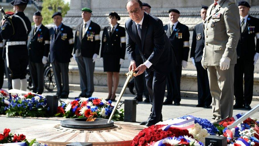 Le président François Hollande ravive la flamme éternelle sur la tombe du soldat inconnu, pour la cérémonie du 8 mai 2016 à Paris