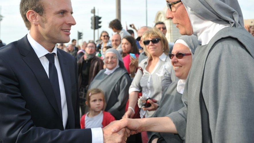 """Emmanuel Macron serre la main d'une religieuse alors qu'il rencontre la foule réunie dans les rues d'Orléans pour les """"fêtes johanniques"""" d'hommage à Jeanne d'Arc le 8 mai 2016"""
