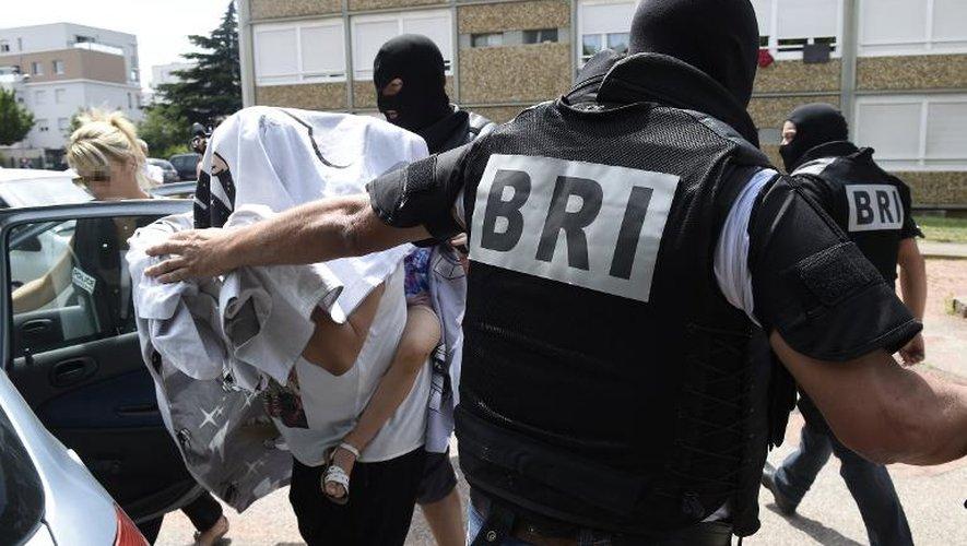 Les forces spéciales de la Brigade de recherche et d'intervention (BRI) escortent une femme et un enfant devant l'immeuble où habite le suspect présumé