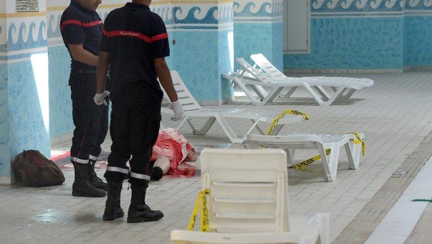 Des secourists tunisiens près du corps d'un touriste tué lors de l'attaque d'un hôtel de la station balnéaire de Sousse, le 26 juin 2015