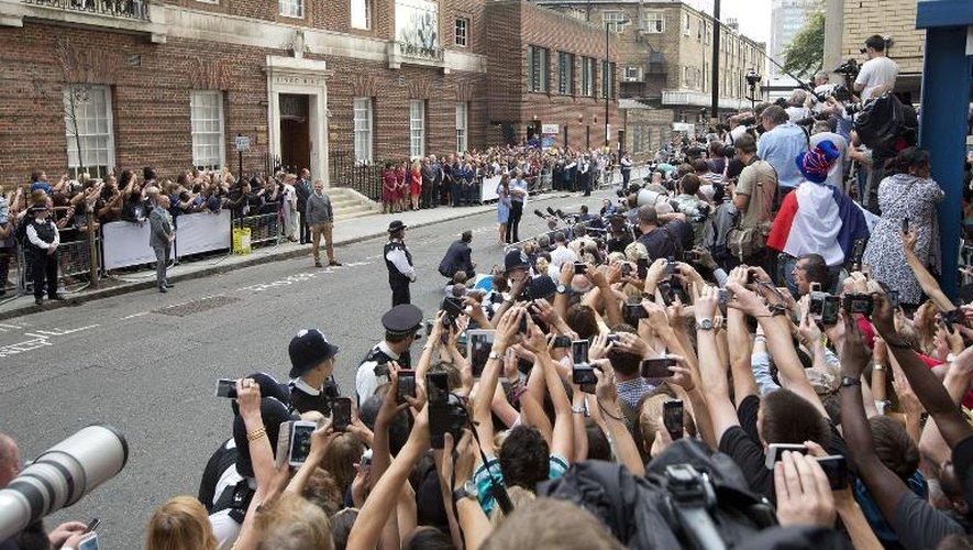Une foule de personnes prenant des photos du prince William et de Catherine, duchesse de Cambridge, pendant que ces derniers leur présentent leur fils devant l'hôpital St Mary, le 23 juillet 2013 à Londres