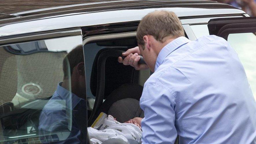 Le prince William installe son fils à l'arrière de son véhicule le 23 juillet 2013 à la sortie de  l'hôpital St Mary de Londres