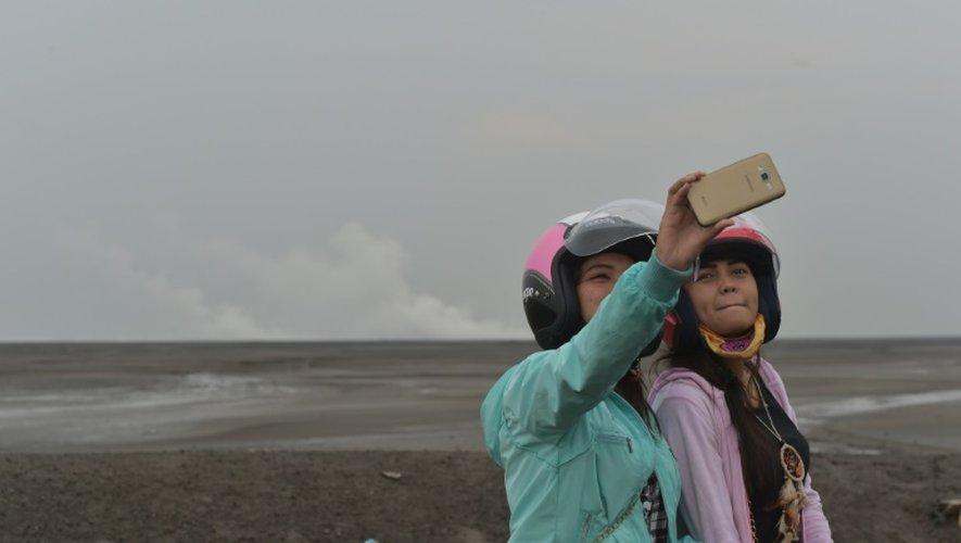 Des touristes prennent des selfies le 28 mars 2016 devant le volcan de boue qui a dévasté  Sidoarjo sur l'île de Java, en Indonésie