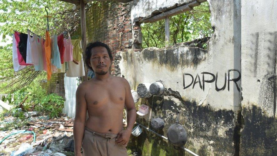 Un Indonésien le 28 mars 2016 dans la maison abandonnée où il vit dans le district de Sidorarjo ravagé le 29 mai 2006 par un volcan de boue