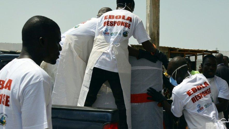 Des employés d'un hôpital font entrer des victimes dans une voiture, le 7 mars 2015 à Monrovia au Libéria