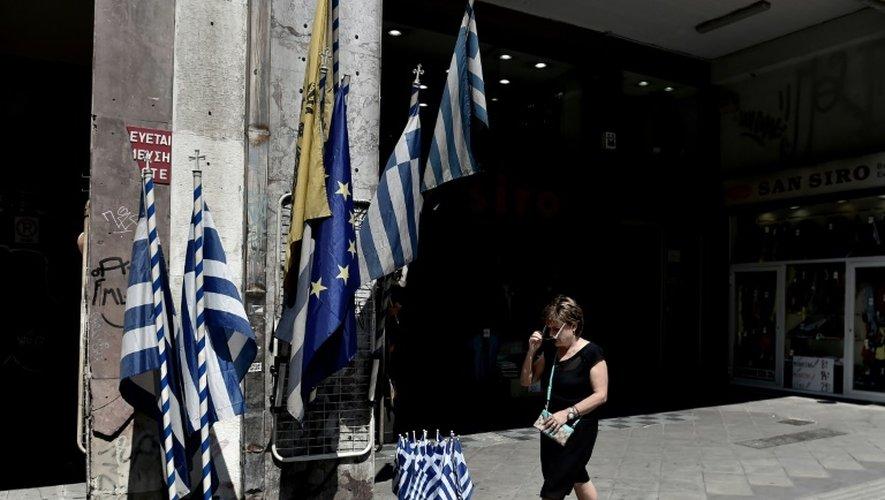 Une femme passe devant des drapeaux grecs dans le centre d'Athènes, le 30 juin 2015