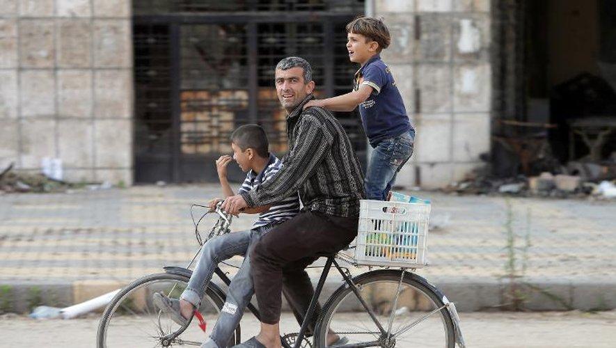 Un homme à vélo transporte deux enfants dans le quartier détruit de la vieille ville à Homs en Syrie, le 12 mai 2014