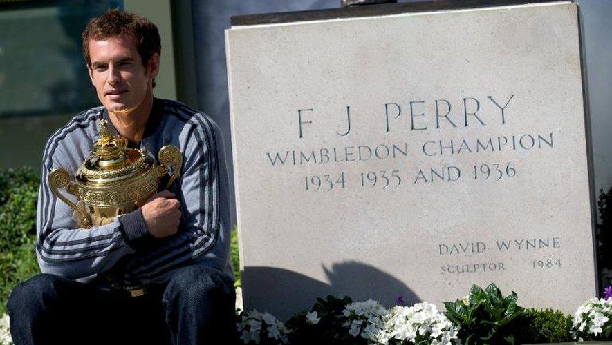 Le champion de tennis britannique Andy Murray pose avec son trophée de Wimbledon 2013 devant une stèle pour Fred Perry