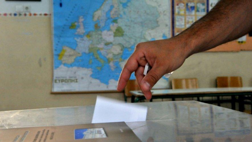 Un homme dépose son bulletin dans l'urne, dans une salle de classe organisée en bureau de vote, à  Thessalonique le 5 juillet 2015