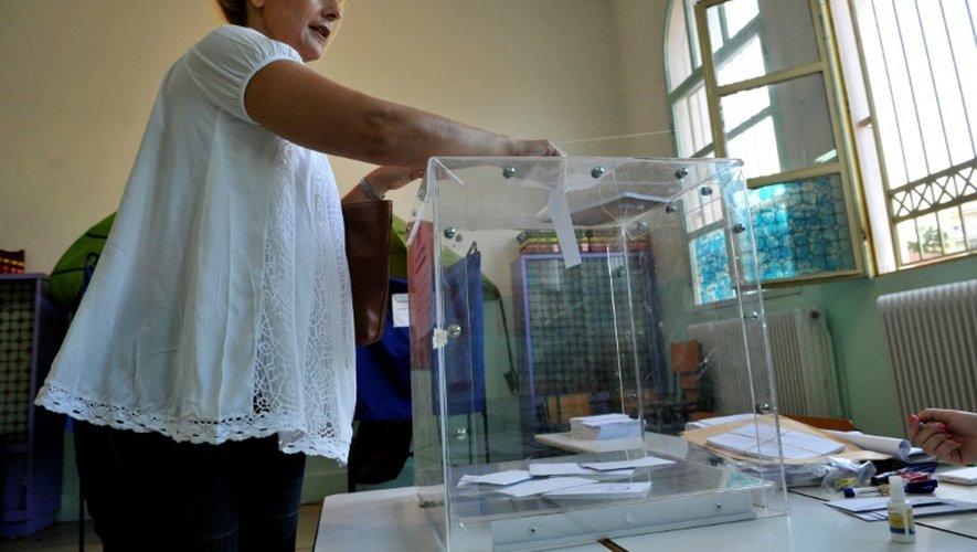 Une femme dépose son bulletin dans l'urne après avoir voté au référendum le 5 juillet 2015, à Thessalonique