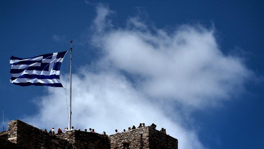 Un drapeau grec flotte au dessus de l'Acropole à Athènes