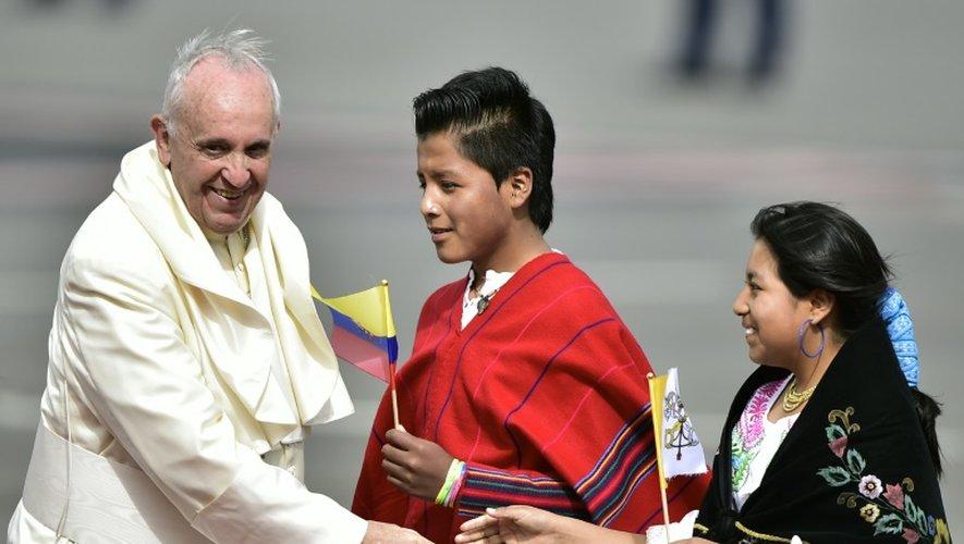 Le pape François salue des enfants l'accueillant à son arrivée à l'aéroport de Quito le 5 juillet 2015