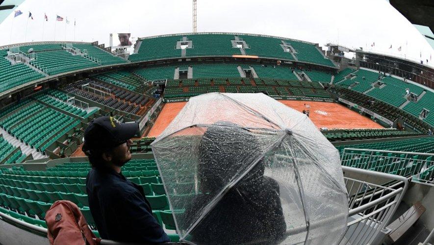 Une personne s'abrite sous un parapluie en attendant le début des matches (finalement annulés) en raison d'une pluie persistante  sur Roland-Garros, le 30 mai 2016
