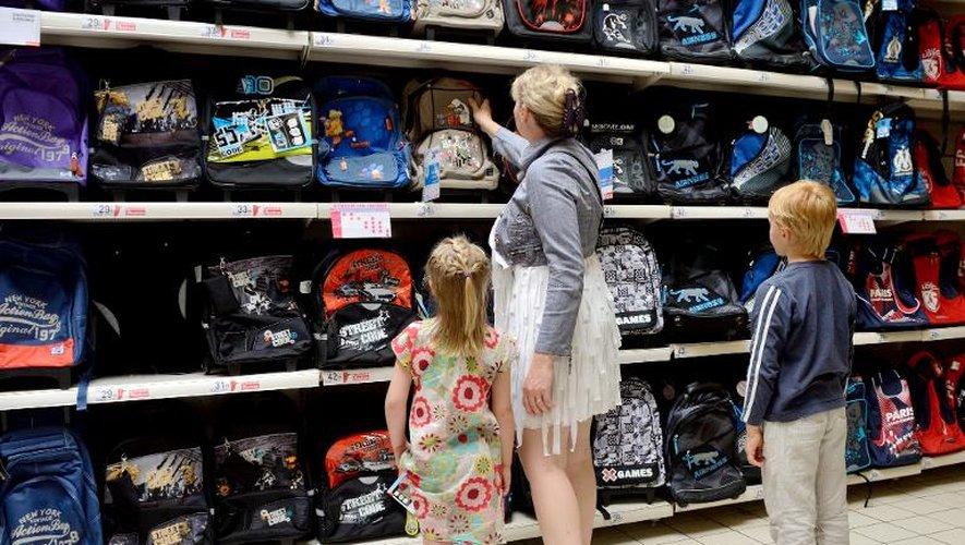 Une mère et ses enfants regardent le rayon des fournitures scolaires dans un supermarché d'Englos, dans le nord de la France, le 9 juillet 2013