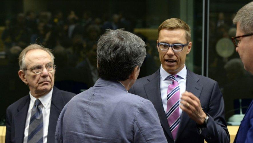 Alexander Stubb (à d.), le ministre finlandais des Finances, s'entretient avec son homologue grec Euclide Tsakalotos sous les yeux de l'Italien Pier Carlo Padoan (à g.) à  l'ouverture de l'Eurogroupe à Bruxelles, le 12 juillet 2015