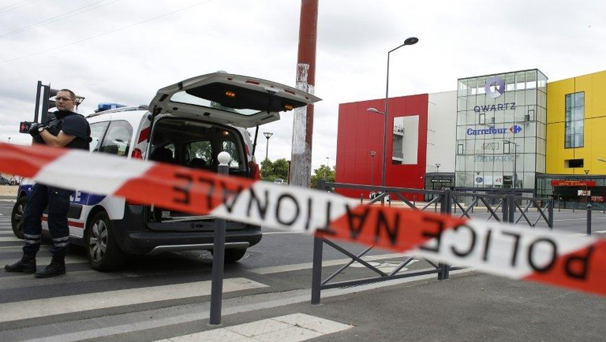 Des policiers empêchent l'accès au centre commercial Qwartz de Villeneuve-la-Garenne (Hauts-de-Seine) après une braquage, le 13 juillet 2015