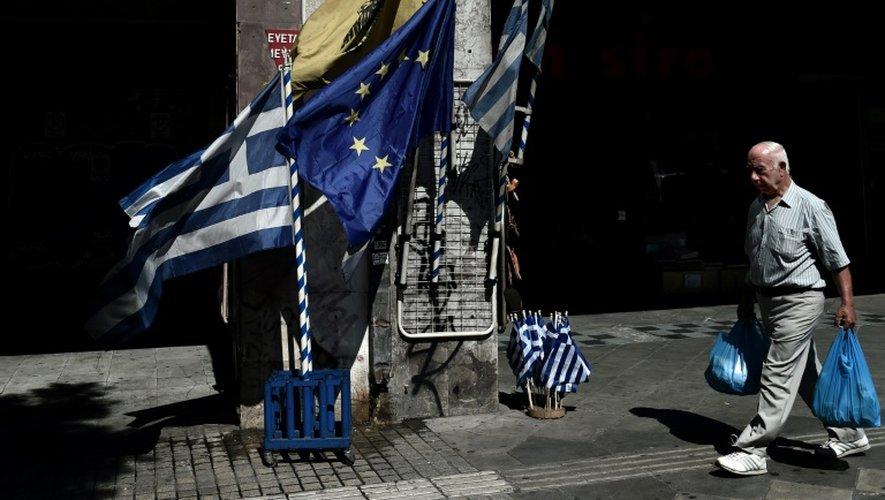 Un homme passe devant des drapeaux grecs et une bannière européene dans une rue du centre d'Athènes, le 13 juillet 2015