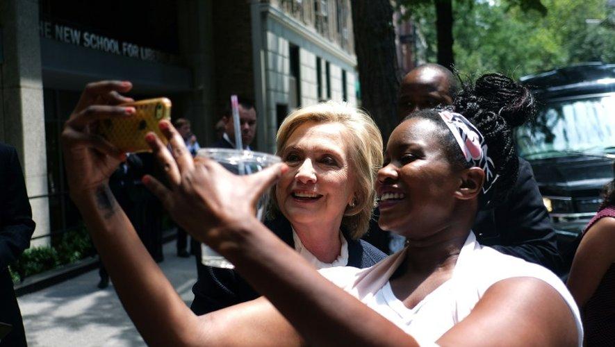 La démocrate Hillary Clinton (g), en campagne pour les présidentielles américaines, pose avec une étudiante le 13 juillet 2015 à New York
