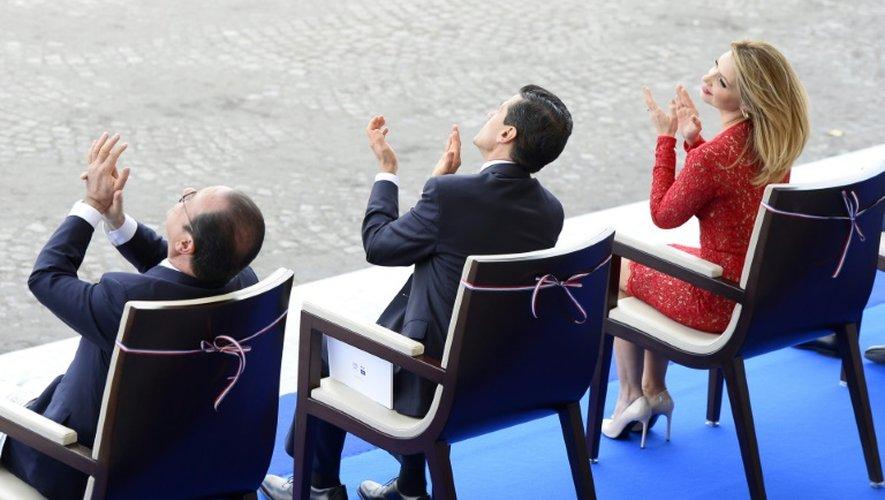 Le président français François Hollande (g) avec le président mexicain Enrique Pena Nieto et son épouse Angelica Rivera applaudissent lors du défilé militaire du 14 juillet 2015 sur les Champs-Elysées