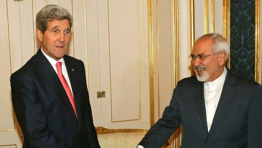 Le secrétaire d'Etat américain John Kerry (g) et son homologue iranien Mohammad Javad Zarif se saluent, le 23 novembre 2015 à Vienne