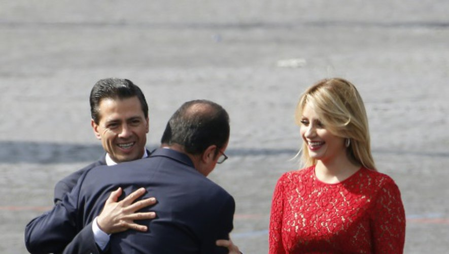 Le président français François Hollande (c) embrasse son homologue mexicain Enrique Pena Nieto (g), aux côtés de la Première dame mexicaine Angelica Rivera le 14 juillet 2015 à Paris
