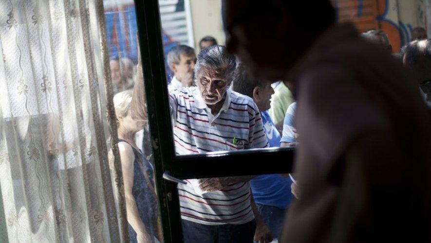 Des grecs attendent de recevoir un repas devant une soupe populaire gerée par l'Eglise, le 14 juillet 2015 à Athènes