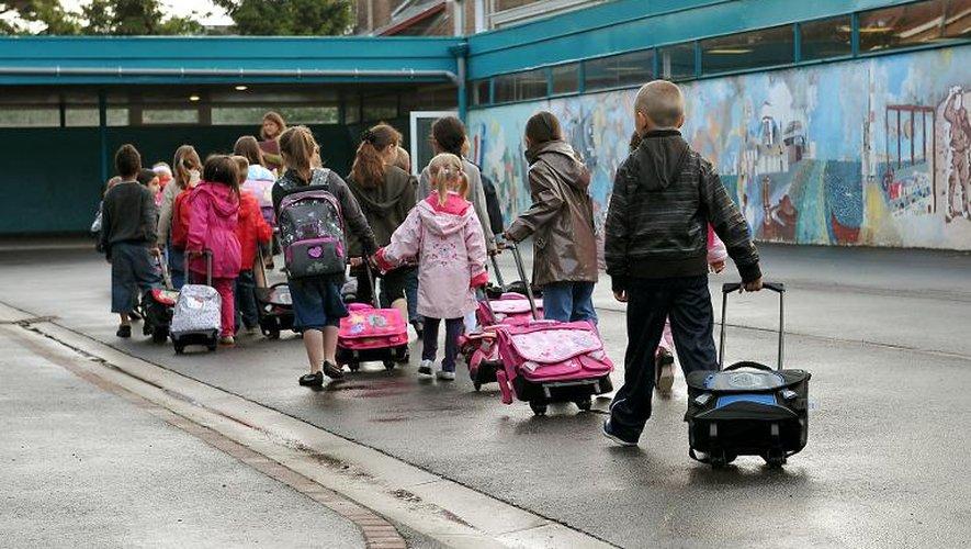 Des enfants marchent dans la cour de leur école, lors de la rentrée scolaire 2011