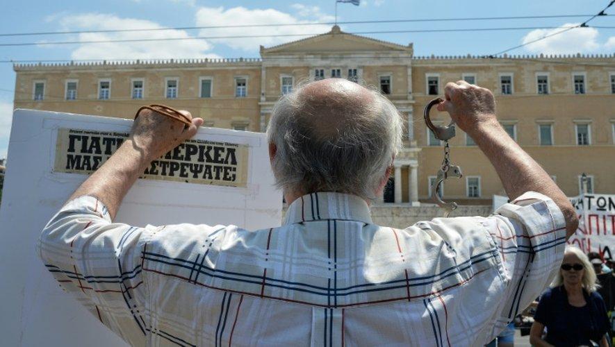 Un manifestant brandit des menottes et une pancarte lors d'une manifestation devant le Parlement grec, le 15 juillet 2015 à Athènes