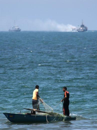 Des pêcheurs palestiniens près d'un bateau de la marine égyptienne touché par une attaque au large de la péninsule du Sinaï, le 16 juillet 2015